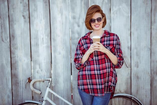 Lächelnde hippie-frau mit dem kaffee und einem fahrrad, stehend