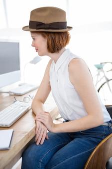 Lächelnde hippie-geschäftsfrau, die an ihrem schreibtisch betrachtet den computer sitzt