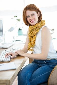 Lächelnde hippie-geschäftsfrau, die an ihrem schreibtisch, einen schal tragend sitzt