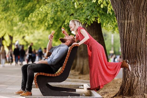 Lächelnde hippie-paare, die spaß haben und eiscreme in der stadt essen. stilvoller junger mann mit bart sitzt auf einer holzbank und blonde frau im roten kleid frau täuscht herum und spielt mit ihm