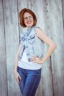 Lächelnde hipster frau mit ihrer hand auf ihrer hüfte,