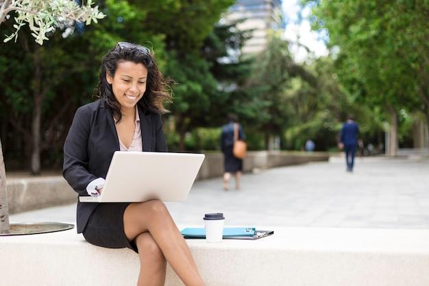 Lächelnde hispanische amerikanische frau, die draußen einen laptopcomputer verwendet. platz für text.