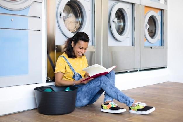 Lächelnde hispanische frau, die auf dem boden sitzt und in der selbstbedienungswäsche liest.