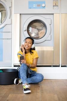 Lächelnde hispanische frau, die auf dem boden sitzt und musik in der selbstbedienungswäscherei hört.