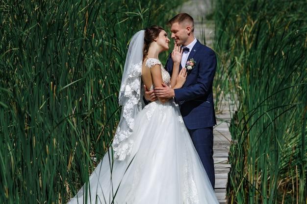 Lächelnde hochzeitspaare, die auf holzbrücke gehen. glückliche braut und bräutigam umarmt leicht und küsst draußen im hohen grünen gras.