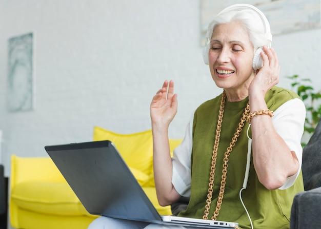 Lächelnde hörende musik der älteren frau auf kopfhörer befestigen auf laptop