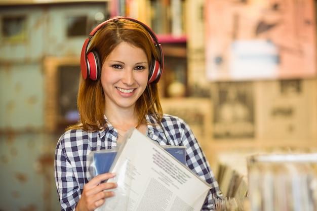 Lächelnde hörende musik der frau und holdingvinyls