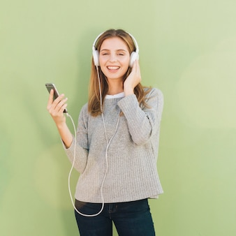 Lächelnde hörende musik der jungen frau auf kopfhörer gegen tadellosen grünen hintergrund