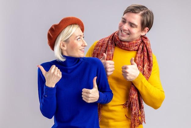 Lächelnde hübsche blonde frau mit baskenmütze und gutaussehender slawischer mann mit schal um den hals daumen hoch und schaut sich am valentinstag an