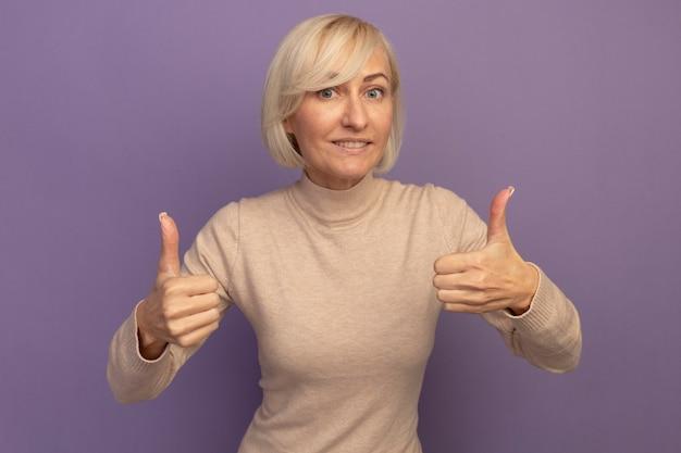 Lächelnde hübsche blonde slawische frau daumen hoch von zwei händen auf lila