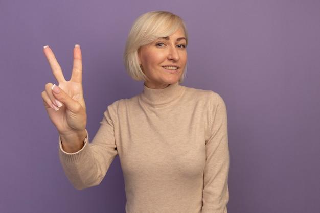 Lächelnde hübsche blonde slawische frau, die siegeshandzeichen auf lila gestikuliert