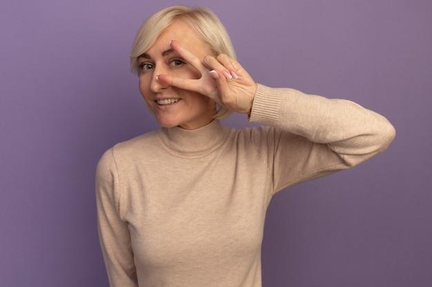 Lächelnde hübsche blonde slawische frau gestikuliert siegeshandzeichen, das kamera durch finger auf lila betrachtet