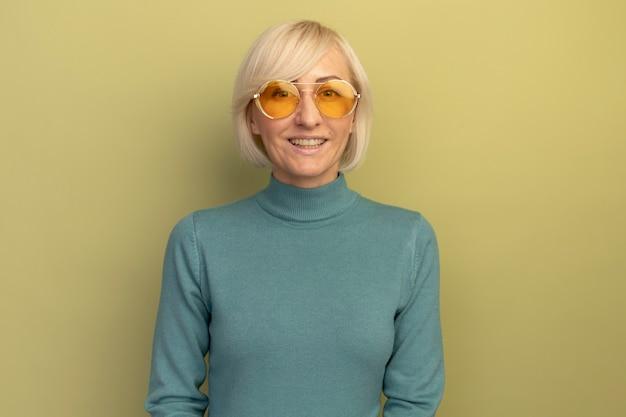 Lächelnde hübsche blonde slawische frau in der sonnenbrille betrachtet kamera auf olivgrün