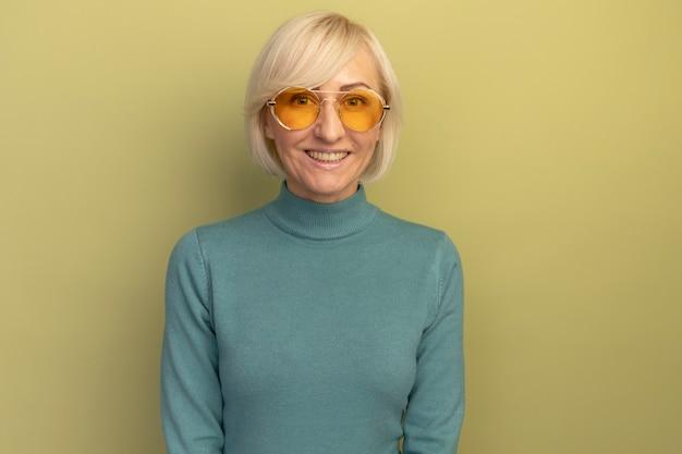 Lächelnde hübsche blonde slawische frau in der sonnenbrille, die kamera auf olivgrün betrachtet