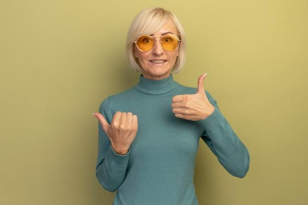 Lächelnde hübsche blonde slawische frau in sonnenbrille daumen hoch und zeigt zur seite auf olivgrün