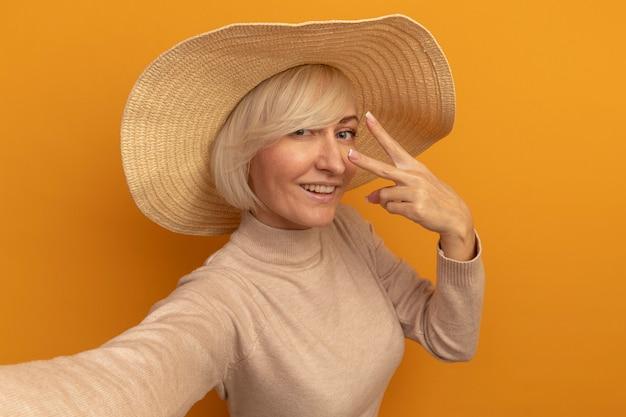 Lächelnde hübsche blonde slawische frau mit strandhut gestikuliert siegeshandzeichen, das kamera auf orange betrachtet