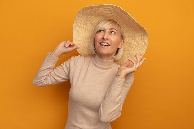 Lächelnde hübsche blonde slawische frau mit strandhut steht mit erhabener hand, die auf orange schaut