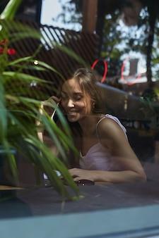 Lächelnde hübsche dame, die per telefon anruft, schoss durch das fensterglas außerhalb des cafés?