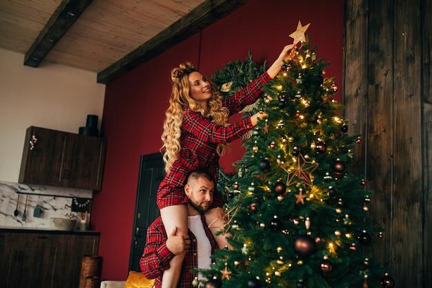 Lächelnde hübsche dame, die schönen weihnachtsbaum mit stern verziert, während sie auf den schultern ihres mannes sitzt