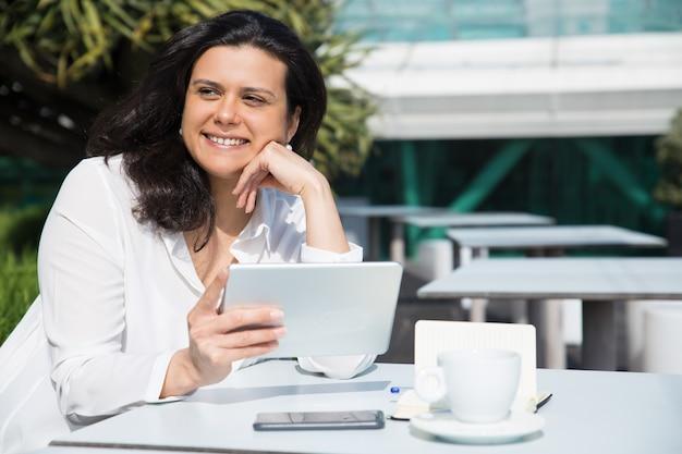 Lächelnde hübsche dame, die tablette im straßencafé bearbeitet und verwendet