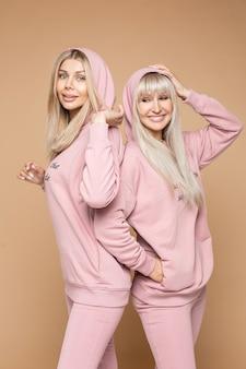 Lächelnde hübsche damen, die bequeme rosa sportanzüge tragen, während sie nebeneinander stehen, während sie kamera betrachten, lokalisiert auf braunem hintergrund
