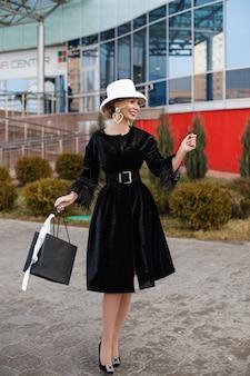 Lächelnde hübsche elegante dame in weißem hut und schwarzem kleid, die auf die straße geht. modestraßenkonzept