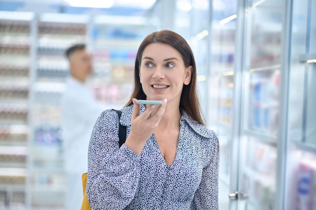 Lächelnde hübsche frau, die an der vitrine der drogerie steht und eine audionachricht auf ihrem smartphone aufnimmt