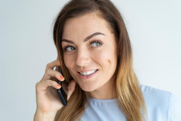 Lächelnde hübsche frau, die auf smartphone spricht. positive dame, die um handy ersucht.