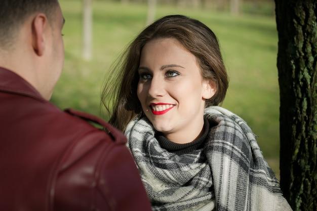 Lächelnde hübsche frau, die freund vor ihr im park am sonnigen tag betrachtet. junges paar in der liebe, mädchen sinnlicher blick, flirten mit freund, erstes date nerven konzept