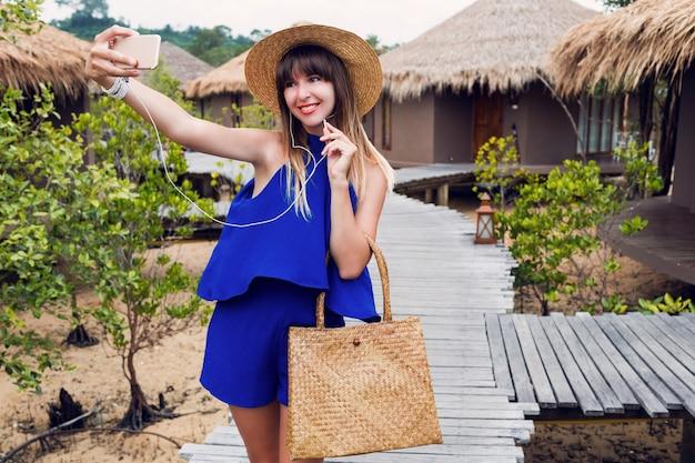 Lächelnde hübsche frau, die selbstporträt durch handy auf ihrem tropischen urlaub in thailand macht. sommer hellblaue kleidung ^ stroh trendigen hut und tasche. rote lippen. gute laune.