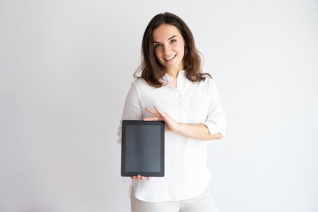 Lächelnde hübsche frau, die tablet-computer hält, seinen schirm zeigt und kamera betrachtet.