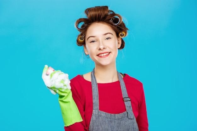 Lächelnde hübsche frau im rosa outfit mit grünen handschuhen