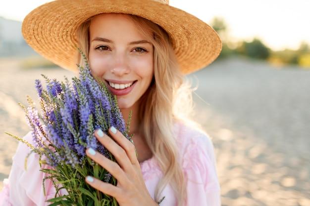 Lächelnde hübsche frau im strohhut, die auf sonnigem strand nahe ozean mit blumenstrauß aufwirft. nahaufnahme porträt.