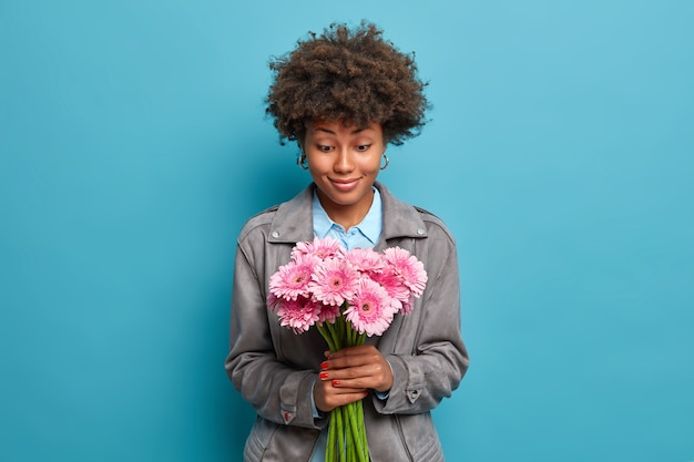 Lächelnde hübsche frau mit natürlichem lockigem haar schaut glücklich auf strauß von gerbera-gänseblümchen