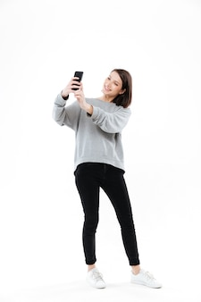 Lächelnde hübsche frau stehend und selfie auf handy nehmend