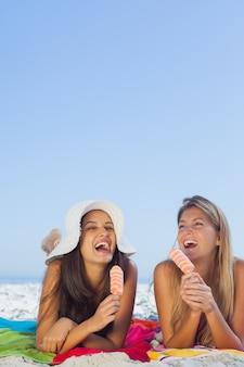 Lächelnde hübsche frauen, die auf ihrem tuch isst eiscreme liegen