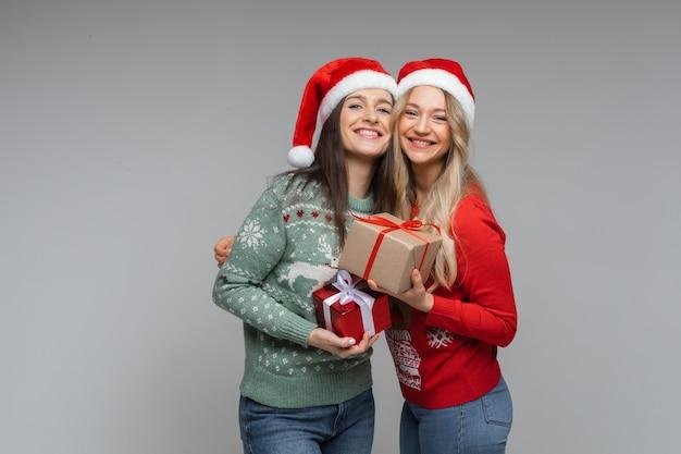 Lächelnde hübsche freundinnen mit weihnachtsgeschenken.