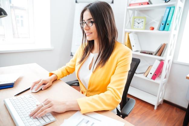 Lächelnde hübsche geschäftsfrau mit tastatur und computermaus im büro