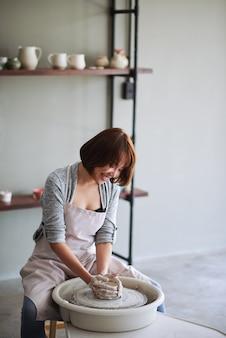 Lächelnde hübsche junge asiatin, die tonvase oder blumentopf in der töpferschule herstellt?
