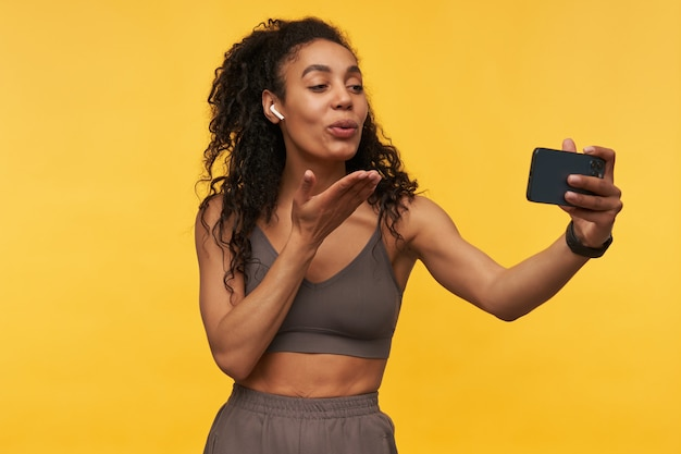 Lächelnde hübsche junge fitnessfrau mit drahtlosen kopfhörern, die einen kuss sendet und ein selfie mit dem smartphone macht, das über gelber wand isoliert ist?
