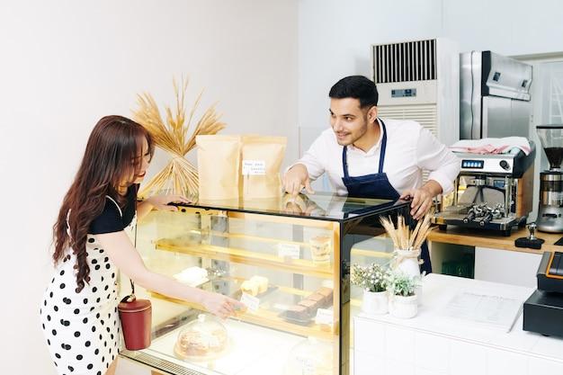 Lächelnde hübsche junge frau, die auf schaufenster zeigt und kellner bittet, ihr ein stück kuchen zu geben