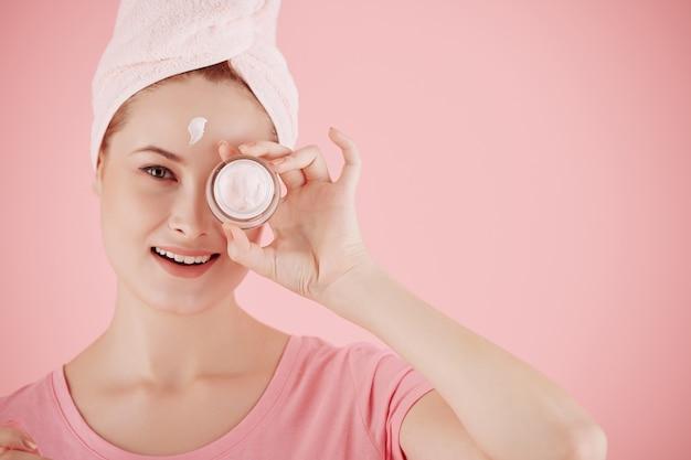 Lächelnde hübsche junge frau, die eine anhebende und aufhellende gesichtscreme zeigt, die sie nach der morgendlichen dusche aufträgt