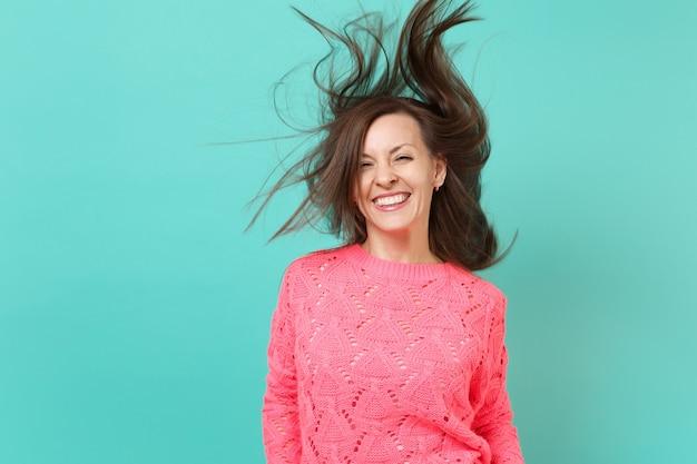 Lächelnde hübsche junge frau in gestricktem rosa pullover mit flatternden haaren einzeln auf blauem türkisfarbenem wandhintergrund, studioporträt. menschen aufrichtige emotionen, lifestyle-konzept. kopieren sie platz.