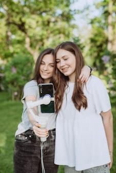 Lächelnde hübsche junge influencer-bloggerinnen filmen oder nehmen videos mit ihrem handy auf einem stabilisator in einem sonnigen grünen park draußen auf. blogging-konzept. weicher selektiver fokus, defokussierung.