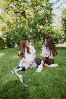 Lächelnde hübsche junge influencer-bloggerinnen filmen oder nehmen videos mit ihrem handy auf einem stabilisator in einem sonnigen grünen park draußen auf. blogging-konzept. weicher selektiver fokus.