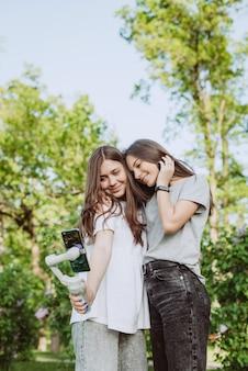 Lächelnde hübsche junge influencer-bloggerinnen filmen oder nehmen videos mit ihrem smartphone auf einem stabilisator in einem sonnigen grünen park draußen auf. blogging-konzept. weicher selektiver fokus.