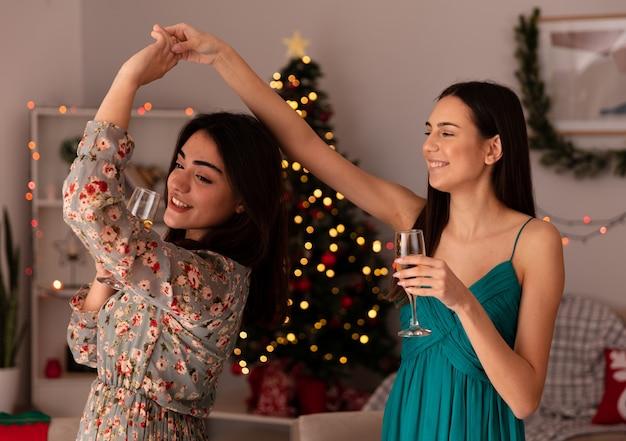 Lächelnde hübsche junge mädchen halten gläser champagner und tanzen zusammen und genießen die weihnachtszeit zu hause
