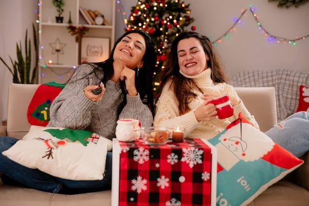 Lächelnde hübsche junge mädchen halten tv-fernbedienung und tasse sitzen auf sesseln und genießen die weihnachtszeit zu hause