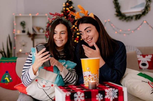 Lächelnde hübsche junge mädchen mit stechpalmenkranz und rentierstirnband betrachten telefon, das auf sesseln sitzt und weihnachtszeit zu hause genießt