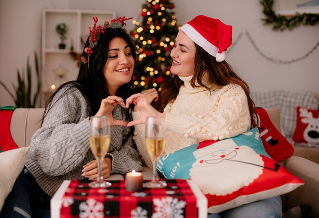 Lächelnde hübsche junge mädchen mit weihnachtsmütze gestikulieren herzzeichen zusammen sitzen auf sesseln und genießen die weihnachtszeit zu hause